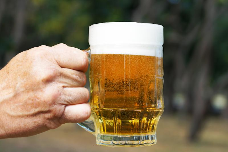 glass mug with beer and foam in a man's hand on the background of nature close up