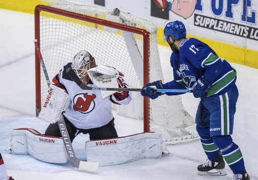 Vancouver Canucks' Josh Leivo, right, watches as a shot from Elias Pettersson gets past New Jersey Devils goalie MacKenzie Blackwood for a goal during the second period of an NHL hockey game Friday, March 15, 2019, in Vancouver, British Columbia. (Darryl Dyck/The Canadian Press via AP)