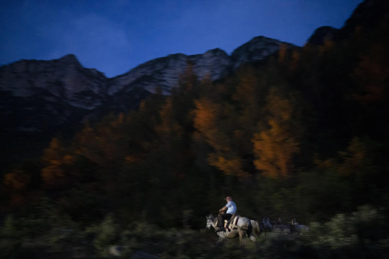 "In this June 22, 2019 photo, Jonuz Jonuzi, 70, rides his horse on the banks of the Vjosa River in the Kelcyre Gorge, Albania. He raised his children here and now watches his grandchildren play in the Vjosa's waters. Before dawn each day, he crosses a bridge over a narrow gorge to tend to his goats before his son drives them to drink from a local spring, where the water emerges cold and crystal clear. ""Everything I have, I have because of the river,"" he says. ""Albania needs electrical energy. But not by creating one thing and destroying another. Why do such damage that will be irreparable for life, that future generations will blame us for what we've done?"" (AP Photo/Felipe Dana)"