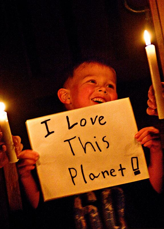 """A young boy holding up a handmade sign reading """"I love this planet!"""" in a candlelit room during Earth Hour 2010, Canada."""