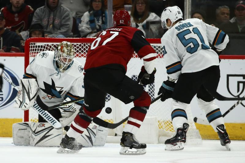 San Jose Sharks goaltender Aaron Dell, left, makes a save on a shot by Arizona Coyotes left wing Lawson Crouse (67) as Sharks defenseman Radim Simek (51) arrives to help with the loose puck during the first period of an NHL hockey game Tuesday, Jan. 14, 2020, in Glendale, Ariz. (AP Photo/Ross D. Franklin)