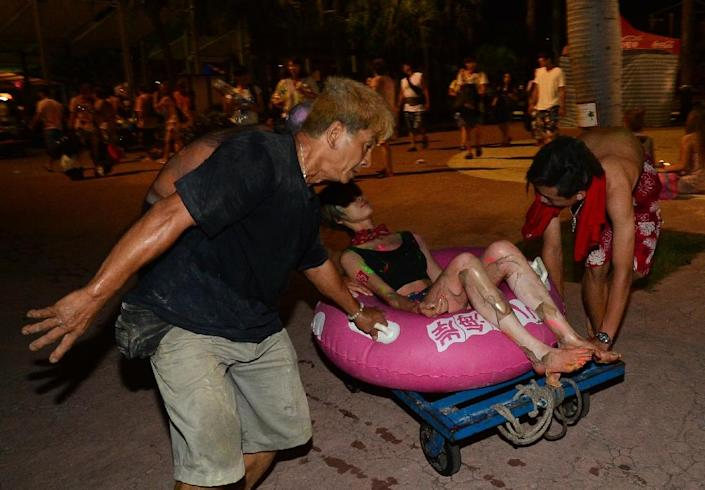 People tend to an injured woman after an explosion at the Formosa Fun Coast amusement park in the Pali district of New Taipei City on June 27, 2015 (AFP Photo/)