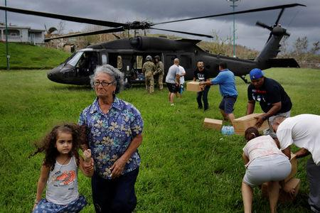 A woman and child walk away as soldiers in a UH-60 Blackhawk helicopter from the First Armored Division's Combat Aviation Brigade deliver food and water during recovery efforts following Hurricane Maria in Verde de Comerio, Puerto Rico, October 7, 2017. REUTERS/Lucas Jackson
