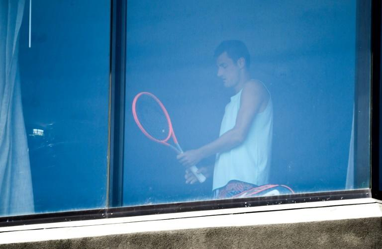 Australian tennis player Bernard Tomic exercises in his hotel room in Melbourne on Sunday as players undergo quarantine ahead of the Australian Open