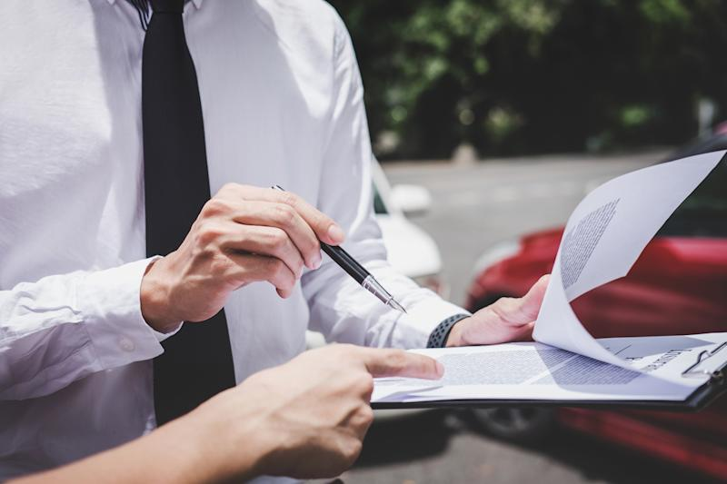 two people reviewing a clipboard of documents with red and white cars in the background