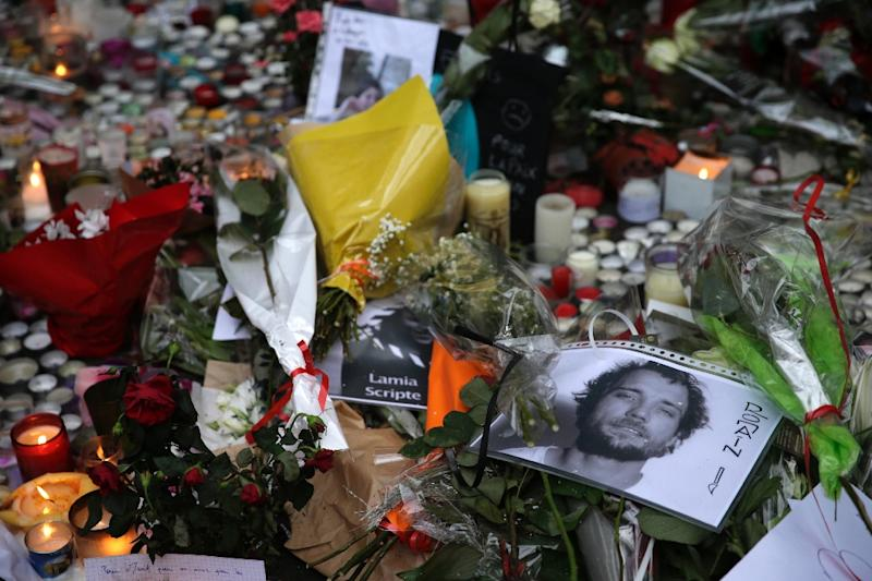 Victims' pictures are seen amongst flowers and candles at the site of the attack at the Cafe Belle Equipe on rue de Charonne in the 11th district, early on November 16, 2015 in Paris (AFP Photo/Kenzo Tribouillard)