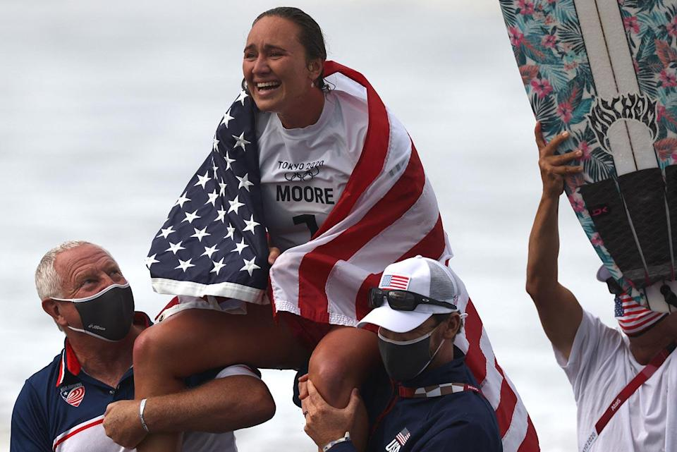 <p>Team USA's Carissa Moore wraps herself in the American flag after winning the women's Surfing gold medal final at Tsurigasaki Surfing Beach July 27.</p>