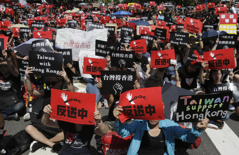 "Hong Kong students and Taiwanese supporters hold slogans reading ""No Extradition to China"" and ""Taiwan Supports Hong Kong"" to oppose Hong Kong's extradition law outside the Legislative Yuan in Taipei, Taiwan, Sunday, June 16, 2019. Hong Kong residents Sunday continued their massive protest over an unpopular extradition bill that has highlighted the territory's apprehension about relations with mainland China, a week after the crisis brought as many as 1 million into the streets. (AP Photo/Chiang Ying-ying)"