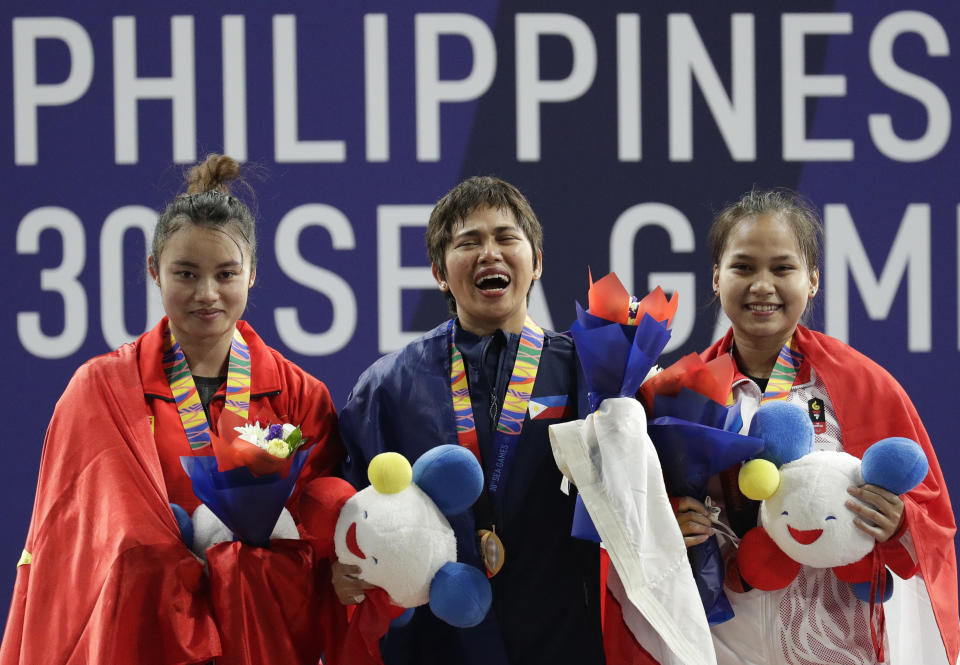 Gold medalist, Philippines' Hidilyn Diaz, center, reacts as she poses for photos beside silver medalist Vietnam's Thi Thuy Nguyen, left, and bronze medalist Indonesia's Juliana Klarisa during the women's 55kg weightlifting at the 30th South East Asian Games at Rizal Memorial Sports Complex in Manila, Philippines on Monday, Dec. 2, 2019. (AP Photo/Aaron Favila)