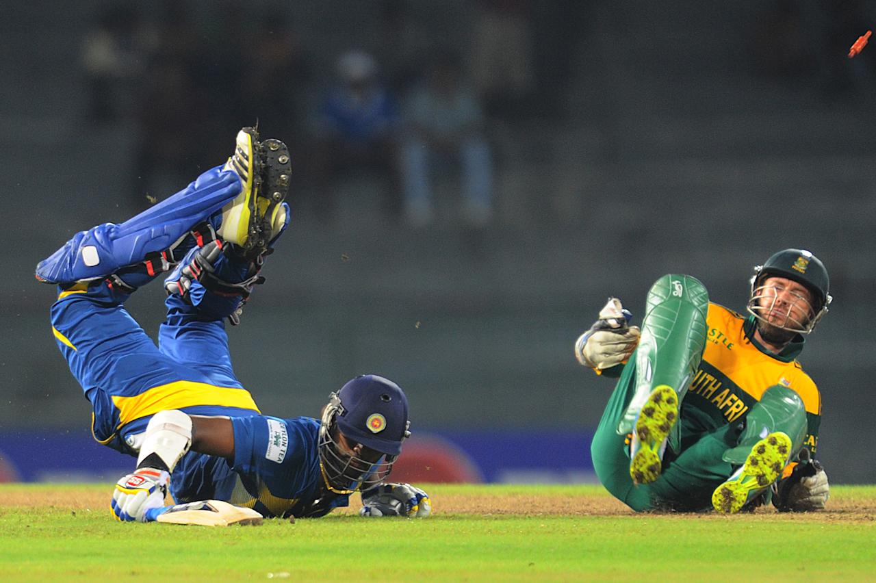 Sri Lankan batsman Thisara Perera (L) dives to get into the crease after a close run-out attempt as South African wicketkeeper AB de Villiers fields a ball during the second One Day International (ODI) match between Sri Lanka and South Africa at the R. Premadasa Stadium in Colombo on July 23, 2013. AFP PHOTO/Ishara S. KODIKARA        (Photo credit should read Ishara S.KODIKARA/AFP/Getty Images)