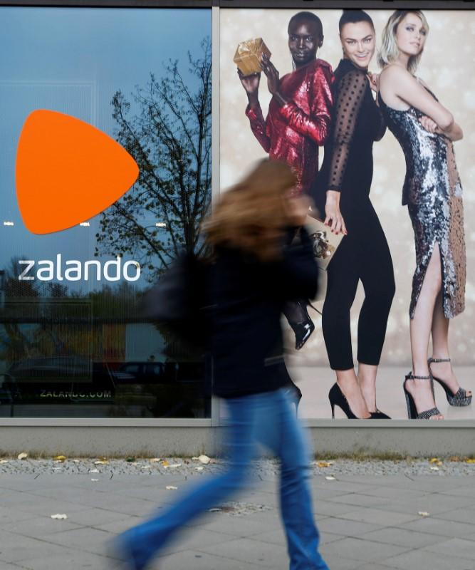 A woman walks past the logo of fashion retailer Zalando in Berlin