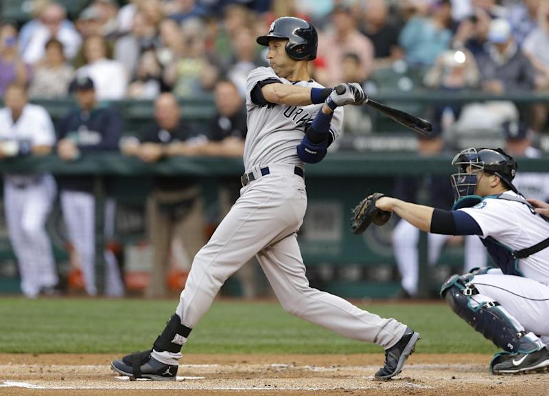 New York Yankees' Derek Jeter, left, singles in the first inning of a baseball game against the Seattle Mariners, Wednesday, June 11, 2014, in Seattle. (AP Photo/Ted S. Warren)