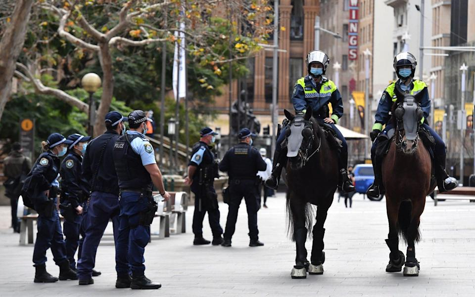 Police patrol George Street in front of Sydney Town Hall in anticipation of an anti-lockdown rally - MICK TSIKAS/EPA-EFE/Shutterstock