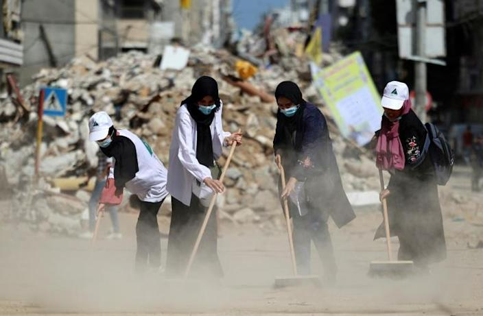 Palestinian volunteers sweep the rubble of buildings, recently destroyed by Israeli strikes, in Gaza City's Rimal district