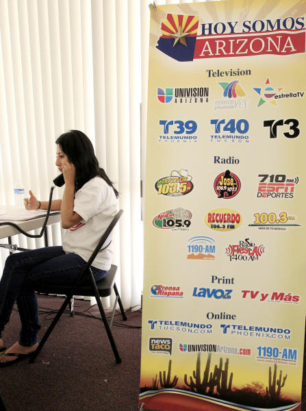 Volunteer Marissa Galindo, of Phoenix, joins a dozen others as they field calls from concerned Hispanics from around Arizona as 23 radio and television stations statewide air a program, Hoy Somos Arizona, reviewing four key provisions of the impact that SB1070 might have on families and individual's rights Wednesday, June 20, 2012, in Phoenix. The program airs prior to the pending United States Supreme Court ruling on the Arizona immigration law that is SB0170. (AP Photo/Ross D. Franklin)
