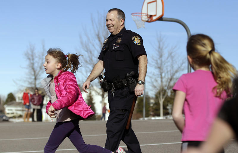 FILE - In this Thursday, Jan. 31, 2013 file photo, Douglas County Sheriff Department Lt. Brian Murphy spends some time on the playground with kids during recess at Buffalo Ridge Elementary School, part of a new cooperative effort between law enforcement and schools for more routine police presence at local primary schools, in Castle Pines, Colo. Since the December school attack in Connecticut, county police have begun a practice of completing their paperwork from their cruisers in elementary school parking lots, and are encouraged to spend more time inside schools. (AP Photo/Brennan Linsley, File)