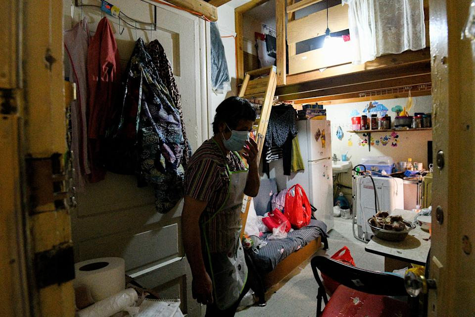 Resident Qin Chan fixes her mask inside of her room in her Chinatown single-room occupancy building, one of many low-income structures that house poor Asian Americans who are at increased risk of COVID-19 as a result of living in tight quarters.