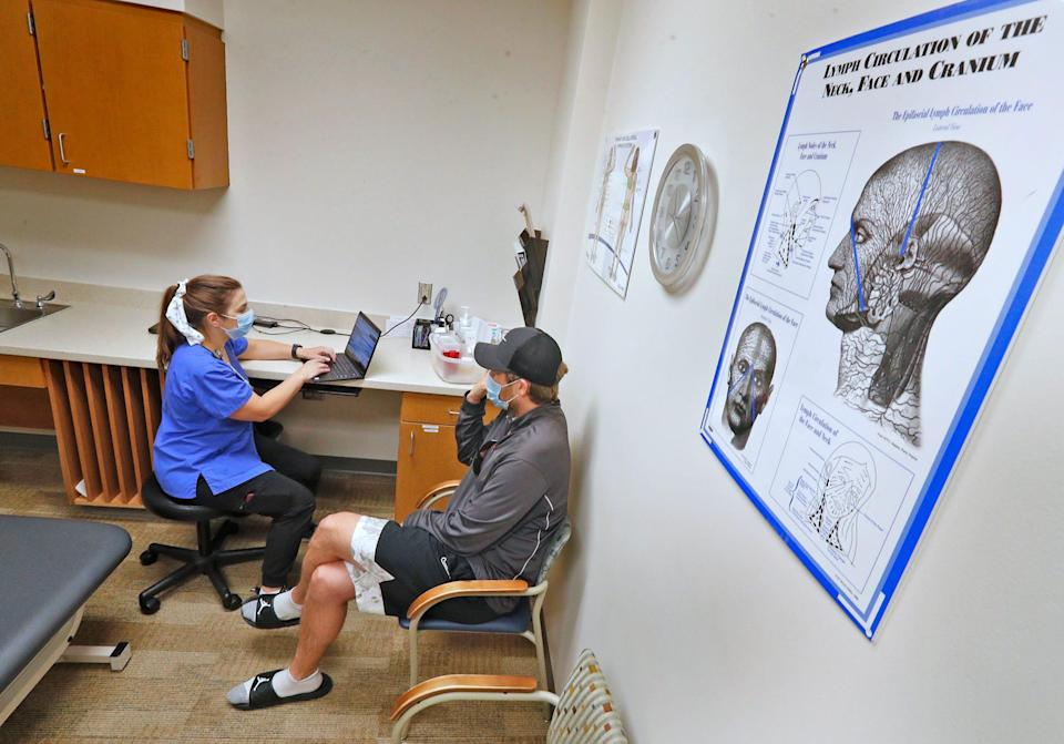 Physical therapist Katherine Morin gets an update from Adam Bodony of Westfield, Indiana, at IU Health North Hospital. The musician was not sick enough to be hospitalized when he was first infected with COVID-19, but he became a long-hauler struggling with head and neck pain.