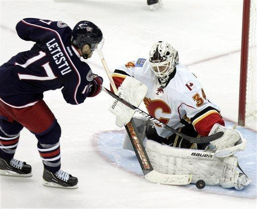 Calgary Flames goalie Miikka Kiprusoff, right, of Finland stops a shot by Columbus Blue Jackets' Mark Letestu in a shoot out period an NHL hockey game in Columbus, Ohio, Tuesday, Dec. 27, 2011. The Flames won 2-1. (AP Photo/Paul Vernon)