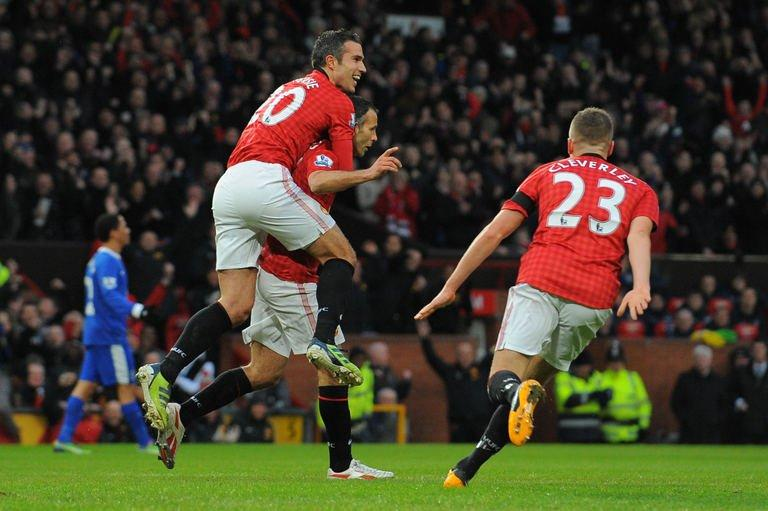 Manchester United's Dutch striker Robin van Persie (L) climbs on the back of Manchester United's Welsh midfielder Ryan Giggs (C) as Manchester United's English midfielder Tom Cleverley (R) runs in to celebrate Giggs's opening goal during the English Premier League football match between Manchester United and Everton at Old Trafford, Manchester, on February 10, 2013. United won 2-0