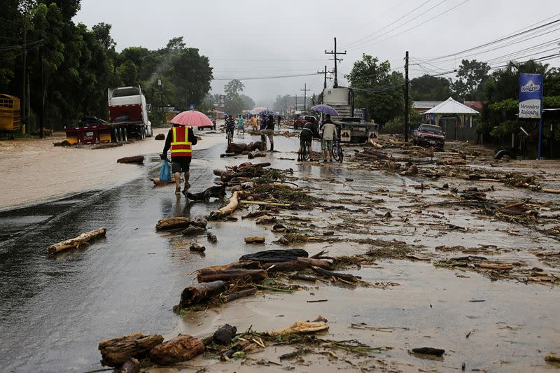 Residents walk along a road with debris dragged by a river during flooding caused by rains from Storm Eta, in Toyos