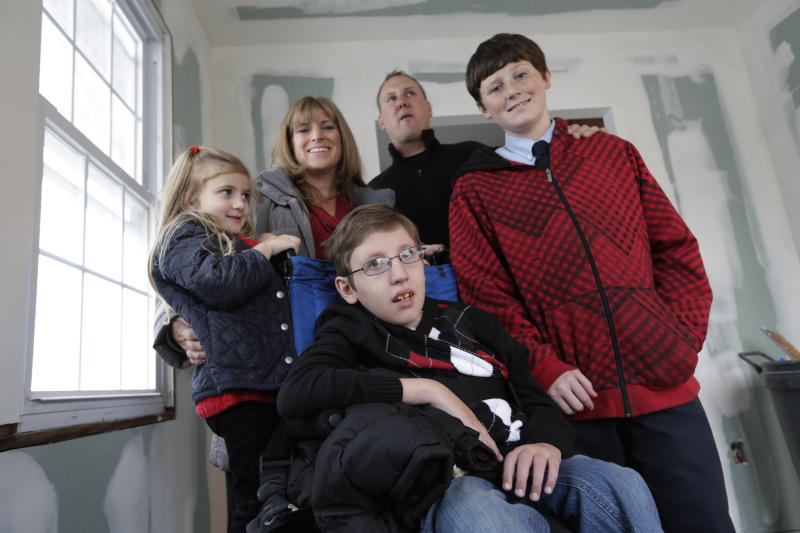 The Troy family poses for a group photo in their Long Beach, N.Y., home., which is under renovation courtesy of Donald Denihan, a stranger who wanted to help a family impacted by Superstorm Sandy,. Wednesday, Dec. 12, 2012. Denihan, who considers himself lucky to have survived three near-death experiences, is paying for renovations to the Troy's home . From left are Katie, 4, mother Kerry Ann, 12 year-old Connor, who suffers from a life-threatening neuromuscular disease, firefighter Chris Troy, and Ryan, 13. (AP Photo/Kathy Willens)