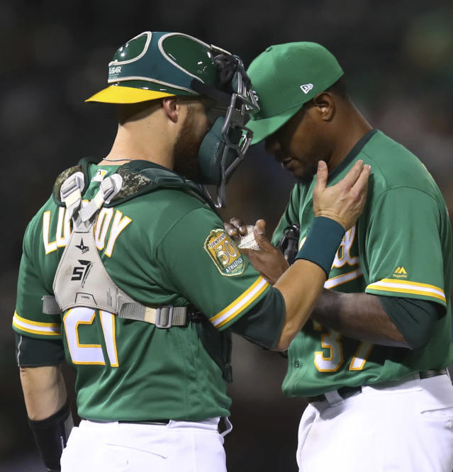 Oakland Athletics' Edwin Jackson, right, meets with Jonathan Lucroy during the fifth inning of the team's baseball game against the Houston Astros on Friday, Aug. 17, 2018, in Oakland, Calif. (AP Photo/Ben Margot)