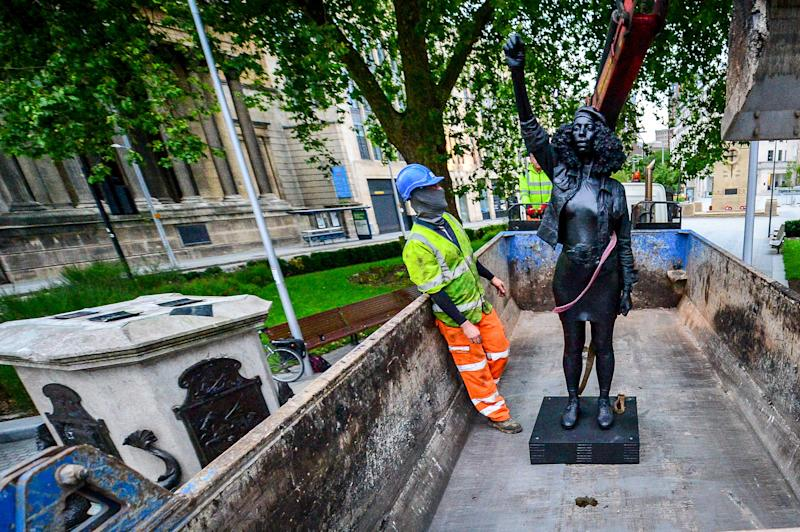 A Surge of Power (Jen Reid) 2020, by prominent British sculptor Marc Quinn, which has been installed in Bristol on the site of the fallen statue of the slave trader Edward Colston, is removed from the plinth and loaded into a recycling and skip hire lorry by contractors.
