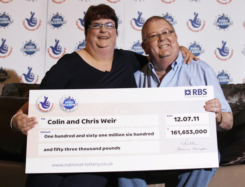 Colin Weir and his wife Chris pose for photographers during a news conference in a hotel near Falkirk, Scotland July 15, 2011. The couple scooped 161 million pounds ($259 million) in Tuesday's Euromillions jackpot. REUTERS/David Moir (BRITAIN - Tags: SOCIETY)