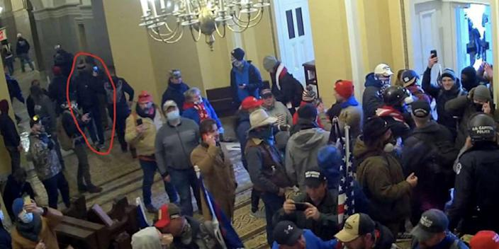 A security footage still from the FBI filing showing a group people inside the Capitol. The man who the FBI believe is Gary Edwards is circled.