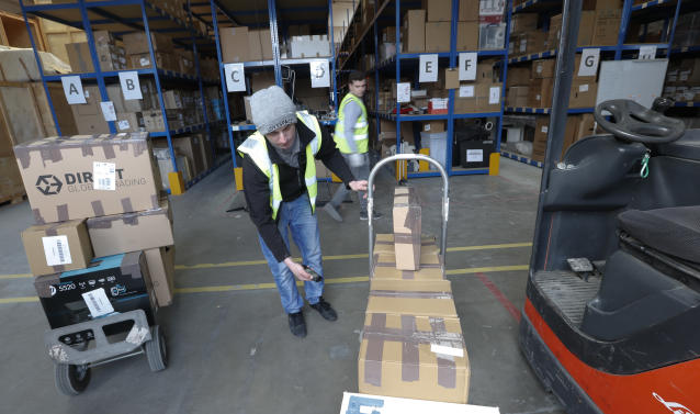 Lovespace warehouse workers Piotr Waligora, front, scans the bar codes as he and and Pawel Mazur unload boxes and goods at the warehouse in Dunstable, England Monday, Jan. 14, 2019. Lovespace, which collects boxes from customers, stores them and then returns the goods when needed, says revenue from businesses doubled over the past year as enterprises large and small began stockpiling inventory because of concerns they will be cut off from suppliers if Britain leaves the European Union without an agreement on future trading relations. (AP Photo/Alastair Grant)