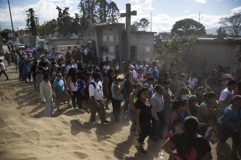People accompany the burial of 14-year-old Madelyn Patricia Hernandez Hernandez, a girl who died in a fire at the Virgin of the Assumption Safe Home, at the Guatemala City's cemetery, Friday, March 10, 2017. Families began burying some of the 36 girls killed in a fire at an overcrowded government-run youth shelter in Guatemala as authorities worked to determine exactly what happened. (AP Photo/Luis Soto)