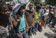 People line up for food aid in Camp Perrin, Haiti, Friday, Aug. 20, 2021, six days after a 7.2 magnitude earthquake hit the area. (AP Photo/Fernando Llano)