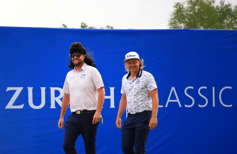 Australia's Marc Leishman rocks a mullet wig in honor of teammate Cameron Smith's signature hairstyle as they walt to the first tee in the third round of the US PGA Tour Zurich Classic of New Orleans