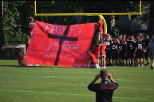 Jon Ross Snell's teammates run through a pregame sign honoring their sick teammate — Caring Bridge