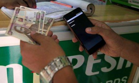 A customer conducts a mobile money transfer, known as M-Pesa, at a Safaricom agent stall, as he holds Kenyan shillings (KSh) in Nairobi, Kenya October 16, 2018. REUTERS/Thomas Mukoya
