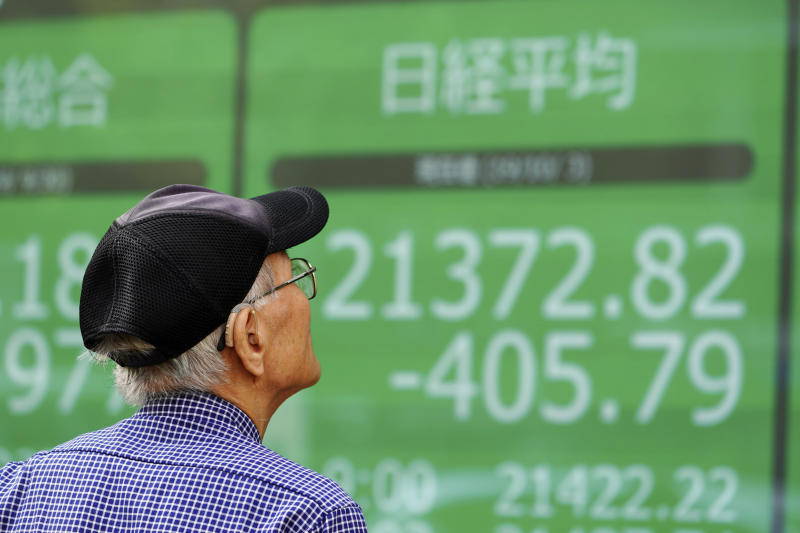 A man looks at an electronic stock board showing Japan's Nikkei 225 index at a securities firm in Tokyo Thursday, Oct. 3, 2019. Asian stocks fell for a fourth day Thursday as weaker U.S. manufacturing and hiring data fueled jitters about the global economy. (AP Photo/Eugene Hoshiko)
