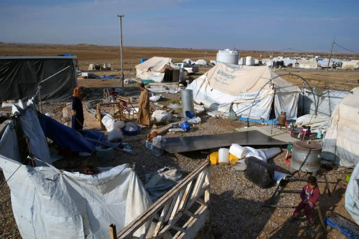 Displaced Iraqis collect their belongings at Hammam Al-Alil camp where they prepare to be evacuated, south of Mosul
