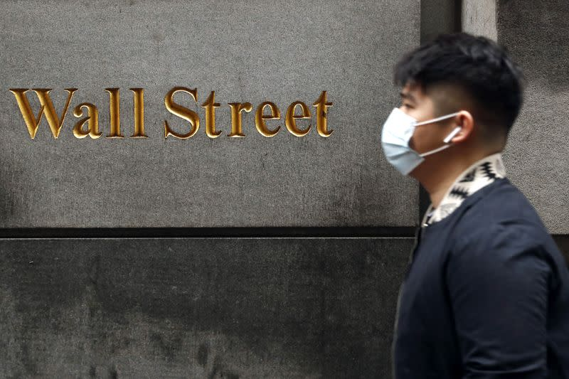 A man wears a protective mask as he walks on Wall Street during the coronavirus outbreak in New York