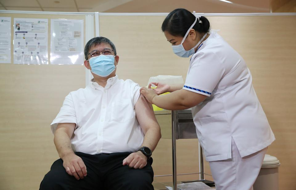 The Ministry of Health's director of medical services Kenneth Mak receiving his COVID-19 vaccination on Friday (8 January). (PHOTO: MCI)