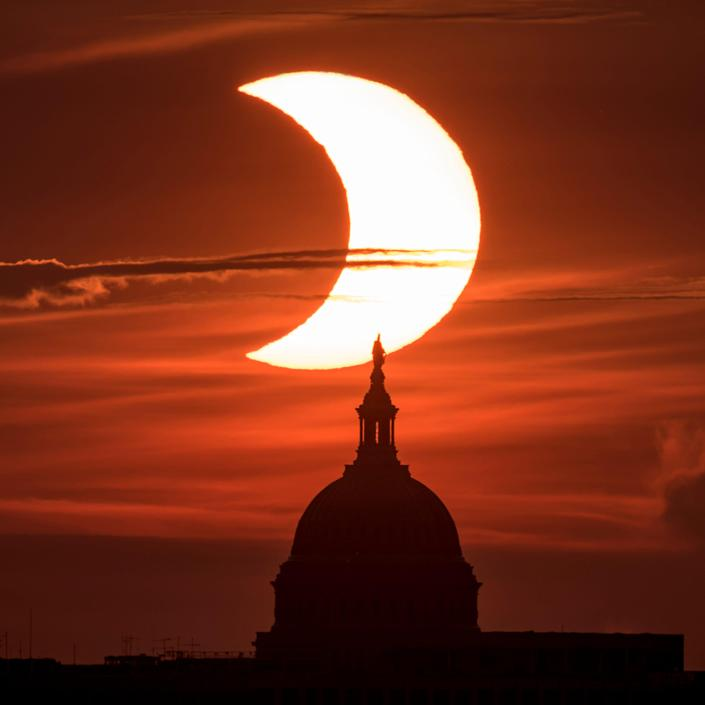 In this handout image provided by NASA, a partial solar eclipse is seen as the sun rises behind the Capitol Building on June 10, 2021 in Arlington, Virginia.