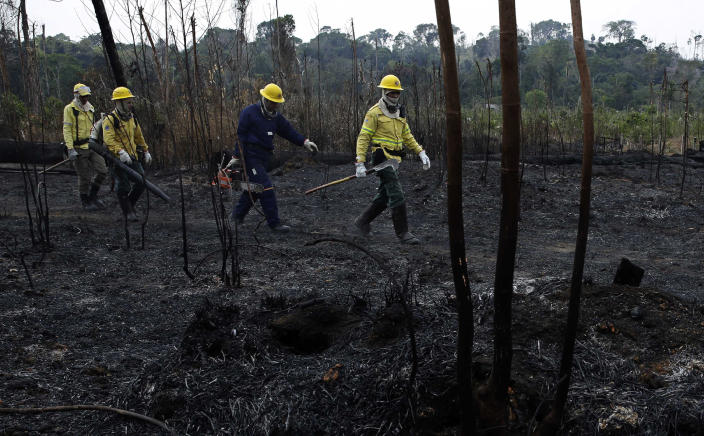 Firefighters walk across charred land to another area as they work to put out fires along the road to Jacunda National Forest in the Vila Nova Samuel region, near the city of Porto Velho in Rondonia state, part of Brazil's Amazon, Aug. 25, 2019. (Photo: Eraldo Peres/AP)