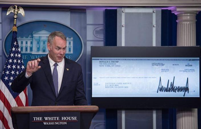 Interior Secretary Ryan Zinke and a check representing President Trump's donation of his first-quarter salary to the National Park Service