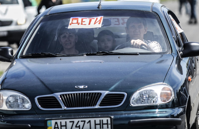 """People drive their car showing a sign reading """"children"""" as they leave their home on July 28, 2014 in Donetsk (AFP Photo/Bulent Kilic)"""