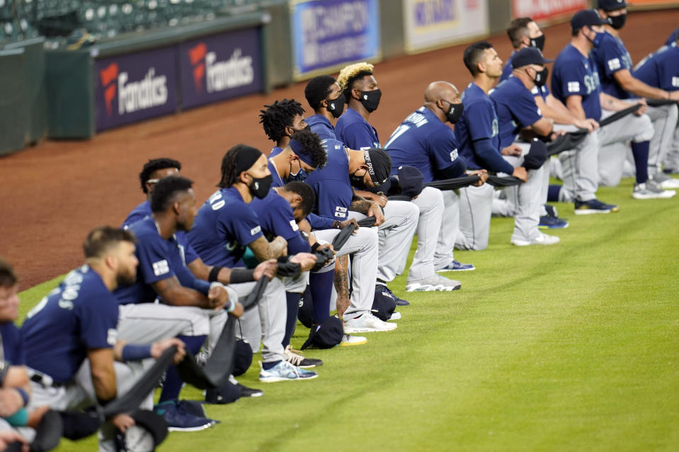 Seattle Mariners players kneel for social justice before a baseball game against the Houston Astros Friday, July 24, 2020, in Houston. (AP Photo/David J. Phillip)
