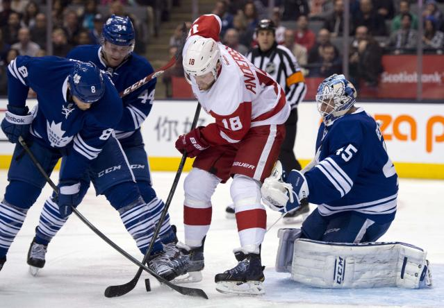 Toronto Maple Leafs defensemen Tim Gleason (8) and Morgan Reilly (44) hold off Detroit Red Wings center Joakim Andersson (18) in front of Maple Leafs goaltender Jonathan Bernier (45) during first-period NHL hockey game action in Toronto, Saturday, March 29, 2014. (AP Photo/The Canadian Press, Frank Gunn)