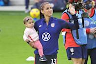 <p>Alex Morgan waves to fans while holding her baby girl Charlie Elena Carrasco after a SheBelieves Cup women's soccer match against Brazil on Sunday in Orlando.</p>