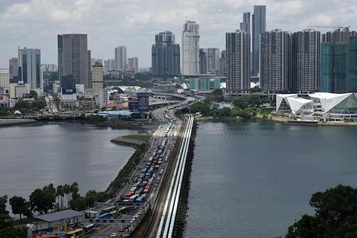Vehicles line up to cross the causeway from southern Malaysia into Singapore on March 17 ahead of a ban on overseas travel announced by Malaysia to curb the spread of the coronavirus.
