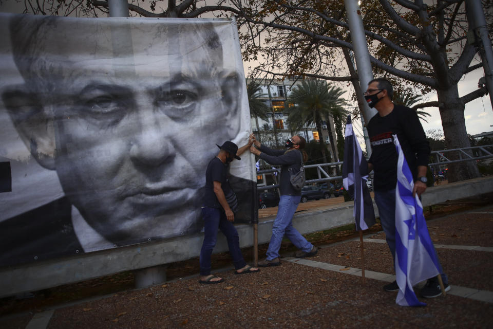 """FILE - In this April 25, 2020 file photo, demonstrators wearing protective face masks amid concerns over the country's coronavirus outbreak, hang a banner showing Israeli Prime Minister Benjamin Netanyahu during """"Black Flag"""" protest against Netanyahu and government corruption, at Rabin Square in Tel Aviv, Israel. After entering the record books last year as Israel's longest-serving prime minister, Benjamin Netanyahu will once again make history on Sunday, May 24, 2020 when he becomes the country's first sitting leader ever to go on trial. (AP Photo/Oded Balilty, File)"""