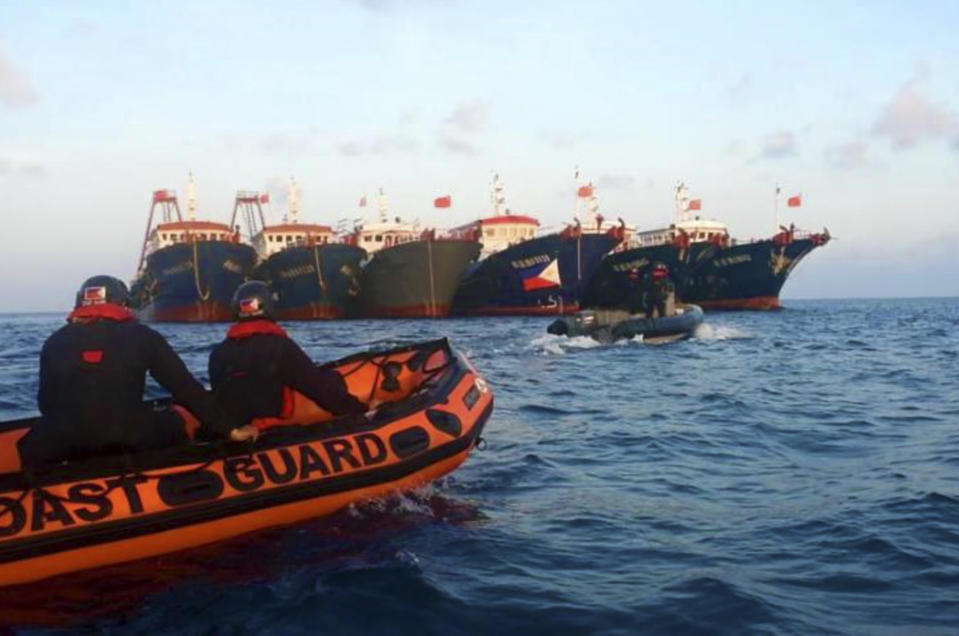 FILE PHOTO: In this handout photo provided by the Philippine Coast Guard, members of the Philippine Coast Guard use rubber boats as they patrol beside Chinese vessels moored at Whitsun Reef, South China Sea on Wednesday April 14, 2021. (Philippine Coast Guard via AP)